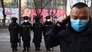 Un hombre pasa por delante de una patrulla de policía, todos ellos con mascarilla, en Pekín.