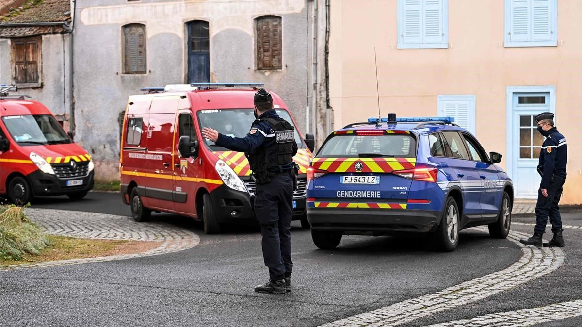 A French Gendarme gestures as fire-fighters trucks drive by in Saint-Just  central France on December 23  2020  after three gendarmes were killed and a fourth wounded by a gunman they confronted in response to a domestic violence call  - The suspect  a 48-year-old man known to authorities for child custody disputes  was  discovered dead  several hours after fleeing the home in an isolated hamlet near Saint-Just  a village south of the city of Clermont-Ferrand  Interior Minister Gerald Darmanin said in a tweet  (Photo by OLIVIER CHASSIGNOLE   AFP)