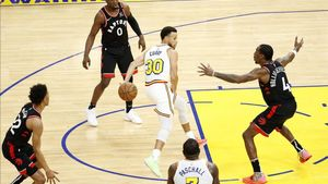 Stephen Curry da un pase por la espalda, rodeado de rivales, en el encuentro de su regreso a los Warriors