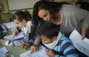 Una madre del colegio Joaquim Ruyra de L'Hospitalet ayuda como voluntaria a un alumno de sexto de primaria en una clase de Matemáticas.