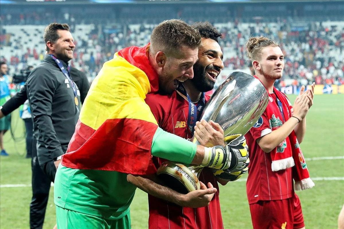 El guardameta Adrián San Miguel, abrazado a Salah que sostiene el trofeo de la Supercopa