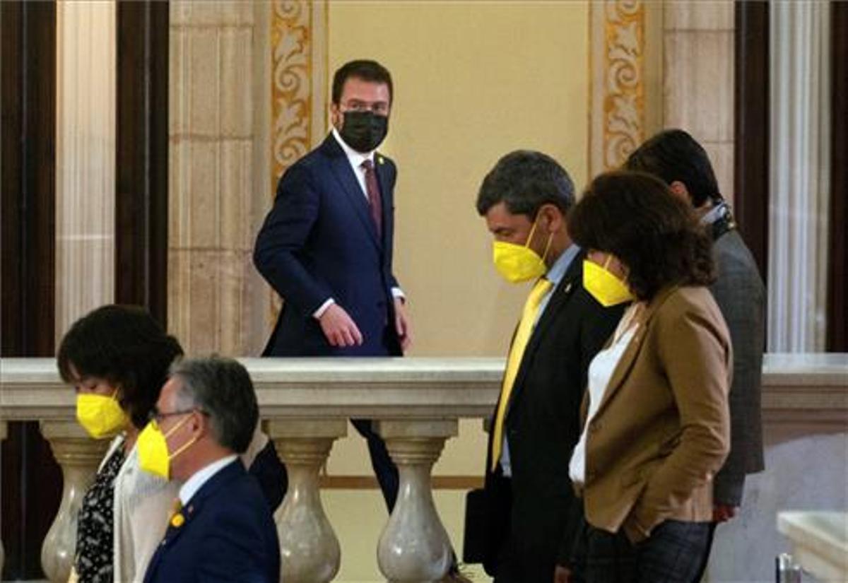 El candidato de ERC, Pere Aragonés, junto a varios diputados de JxCat, en los pasillos del Parlament durante un receso del debate de investidura del nuevo presidente de la Generalitat.