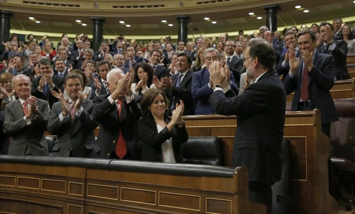 El grupo parlamentario, varios ministros y la vicepresidenta, Soraya Sáenz de Santamaría, aplauden a Mariano Rajoy tras ganar la votación del debate de investidura, el pasado sábado 29 de octubre.