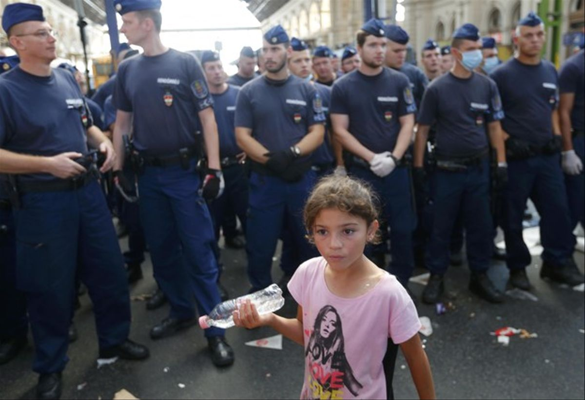 Una niña fotografiada frente a los policías que impiden la entrada de inmigrantes en la estación de trenes de Keleti, en Budapest, este martes.