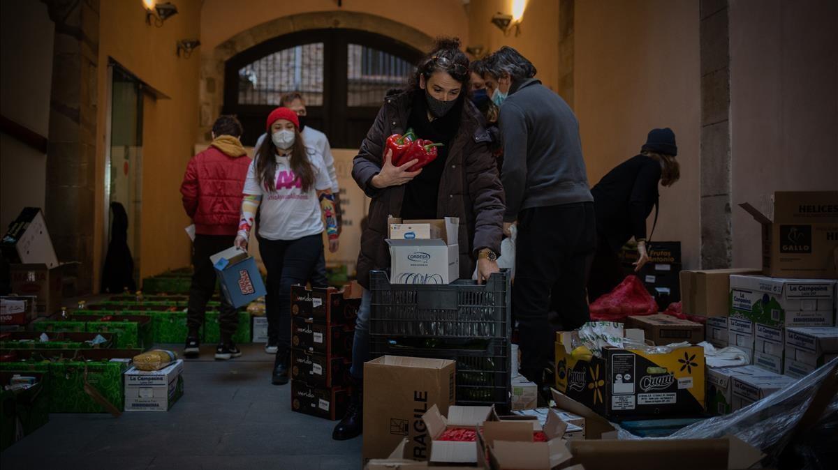 Varios voluntarios de la asociacion Actua Ayuda Alimenta (AAA) preparan cestas de alimentos para trabajadores del sector cultural en Barcelona.