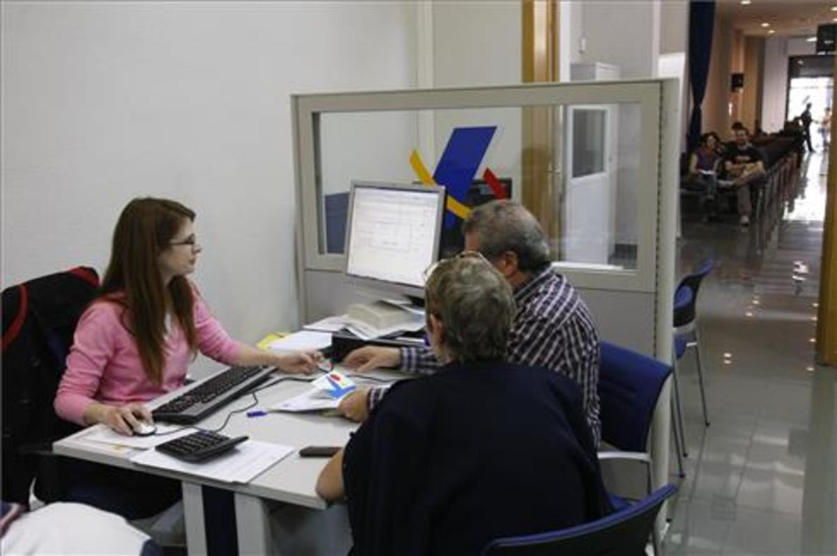 Una pareja hace la declaración de la Renta en una oficina de la Agencia Tributaria en Barcelona.