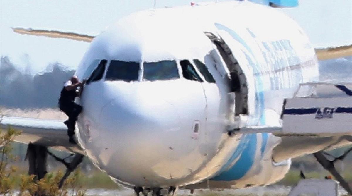 Un hombre escapa del avión secuestrado por una de las ventanillas de la cabina del piloto.