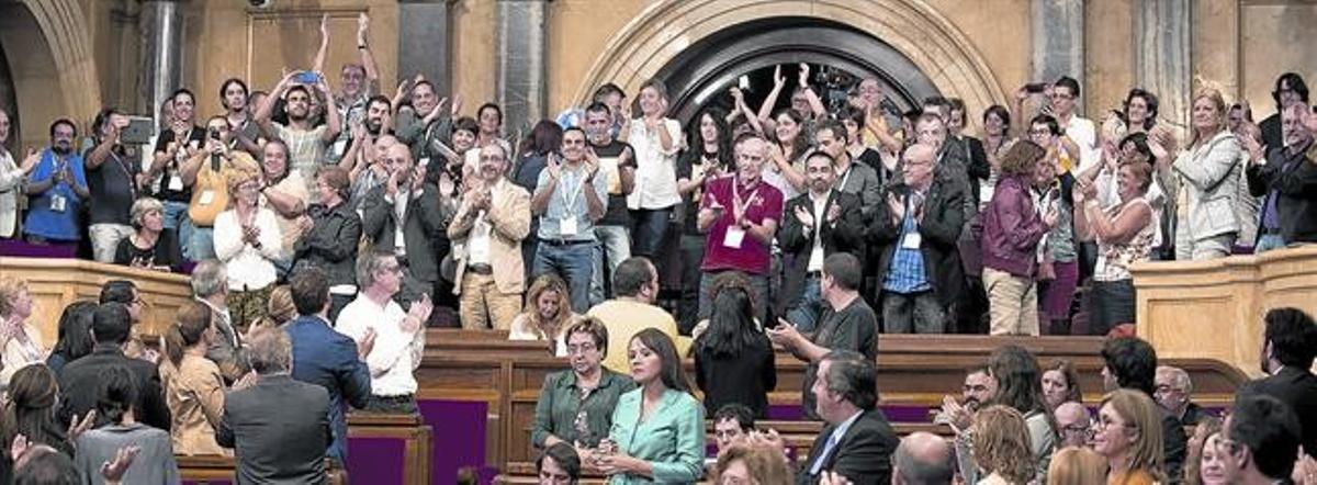 La tribuna de invitados del Parlament aplaude tras la aprobación de la ley, ayer.