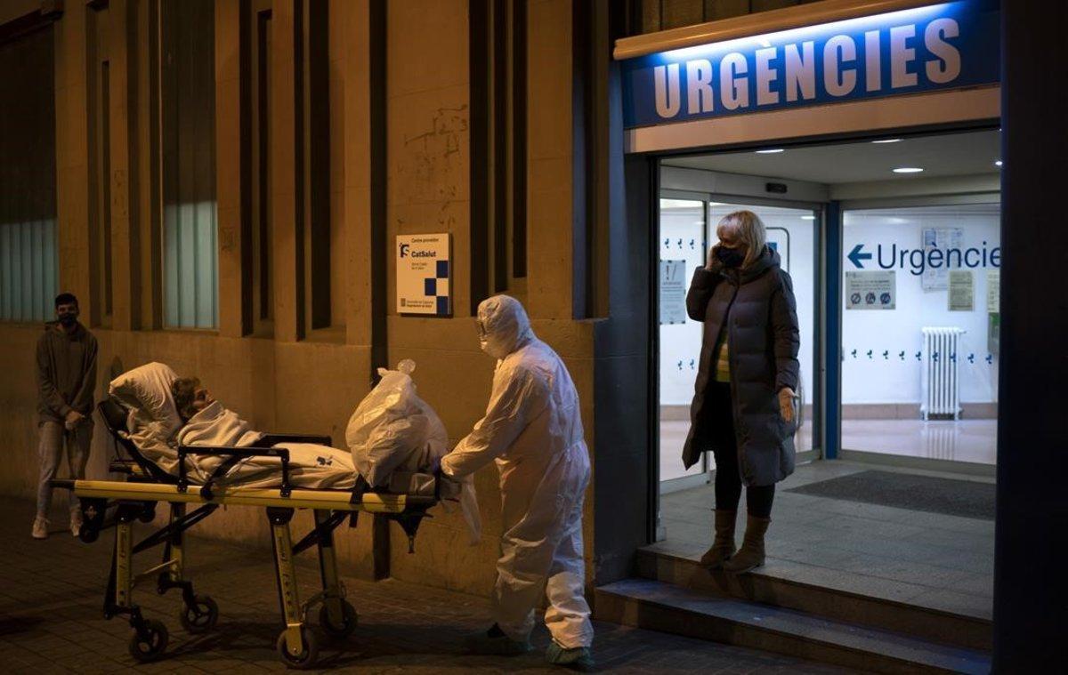 Un paciente es llevado a una ambulancia desde un hospital de Barcelona.