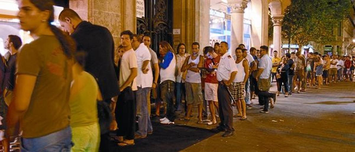 Cola de clientes ante la tienda de Orange en el paseo de Gràcia de Barcelona, el jueves por la noche.