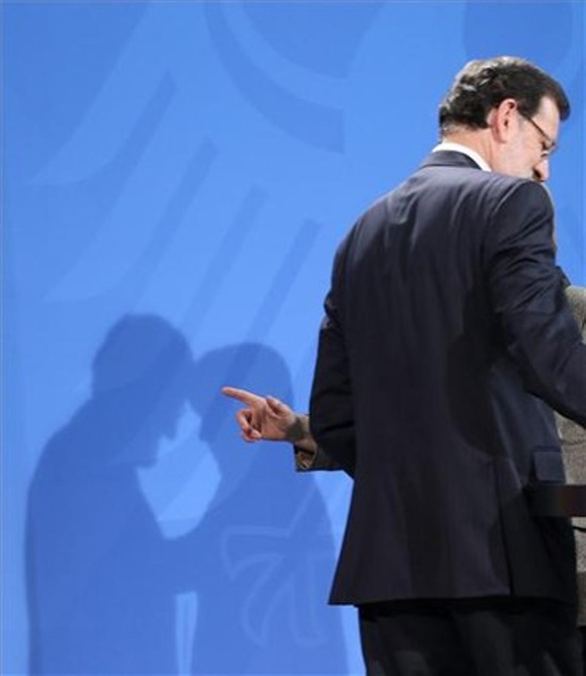 Las sombras de Rajoy y Merkel, durante su rueda de prensa del lunes, en Berlín.