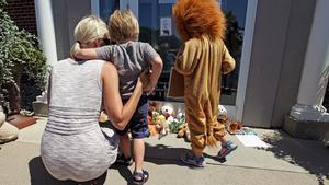 Uns nens ploren la mort de Cecil, davant la porta de la clínica del dentista que el va matar, a Bloomington Minneapolis.