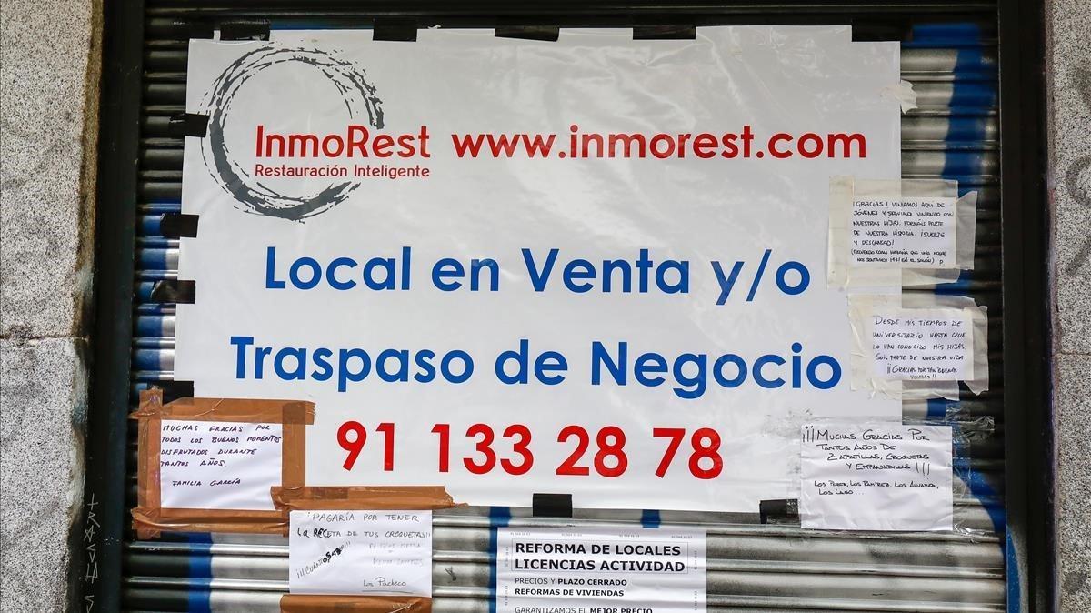 Cartel que anuncia la venta o traspaso en la persiana de una cafetería de Madrid.