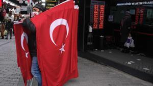 Un hombre vende banderas de Turquía frente a una oficina de cambio de moneda en Estambul.
