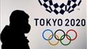 Una persona pasa delante del logotipo de Tokio 2020
