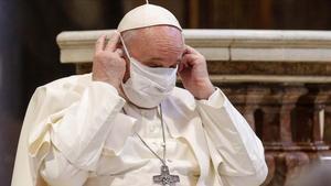 El papa Francisco se coloca una mascarilla durante un acto de oración.