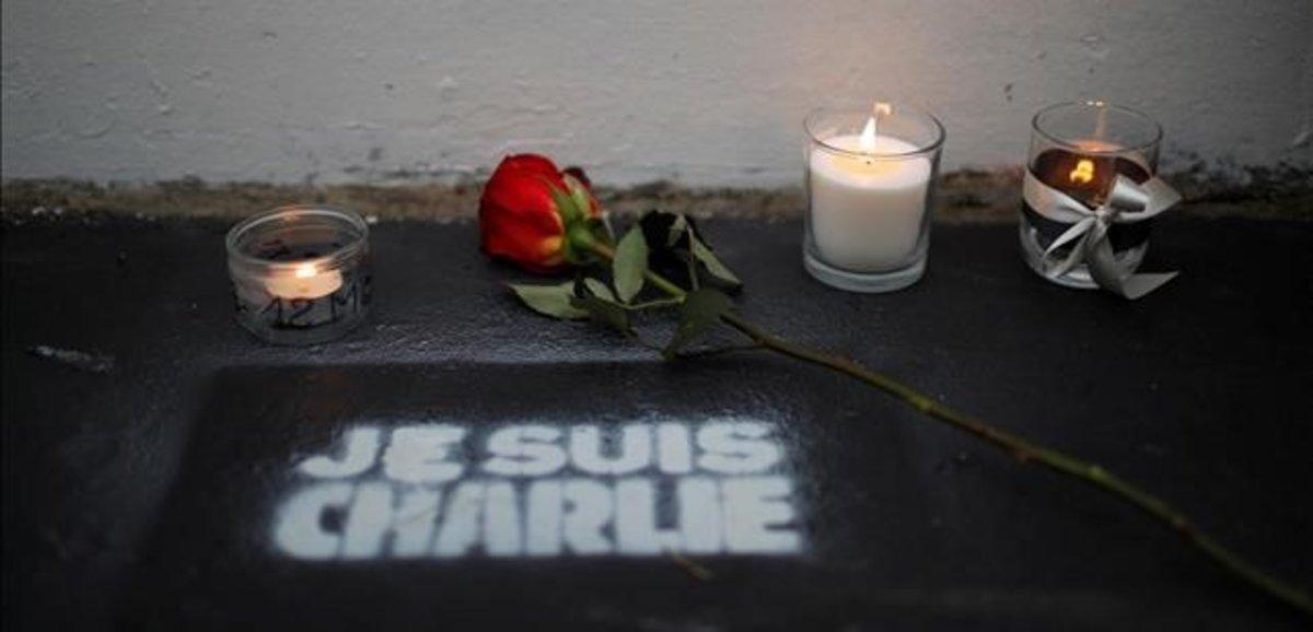 Flores y velas ante la antigua redacción de Charlie Hebdo en el quinto aniversario de la matanza.