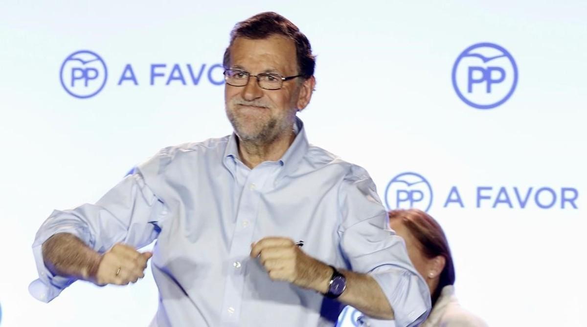 El líder del PP en el balcón de la sede del partido, tras la victoria electoral.