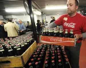 Trasiego de botellas de coca-cola en una embotelladora.