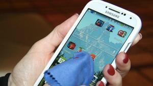 Limpieza con una bayeta de la pantalla de un móvil Samsung.