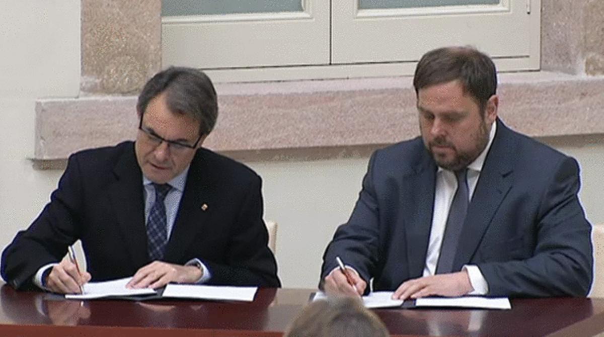 Artur Mas y Oriol Junqueras firman el pacto de gobernabilidad.