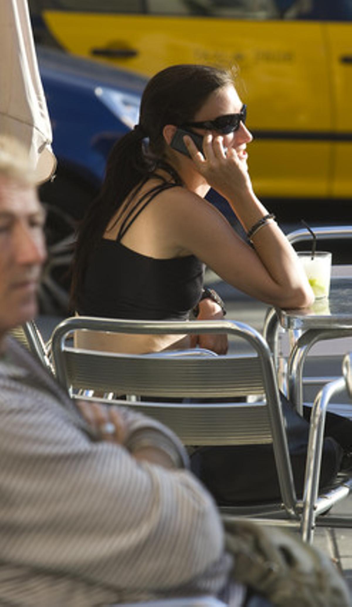 Una chica habla por teléfono móvil, en una terraza de Barcelona.