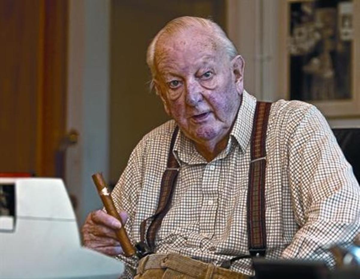 Tom Sharpe, en su casa de Llafranc, sentado frente a su máquina de escribir con un puro en la mano.