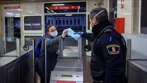 Un policía reparte mascarillas en la estación de tren de Alcalá de Henares, el pasado 13 de abril.