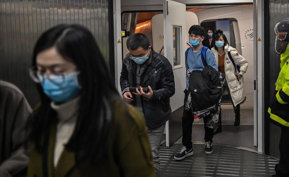 Pasajeros con mascarilla salen de un avión, tras aterrizar en el aeropuerto de Wuhan.