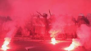 Una barreda de policías antidisturbios vigilan a los manifestantes en medio de una densa humareda que sale de las antorchas.