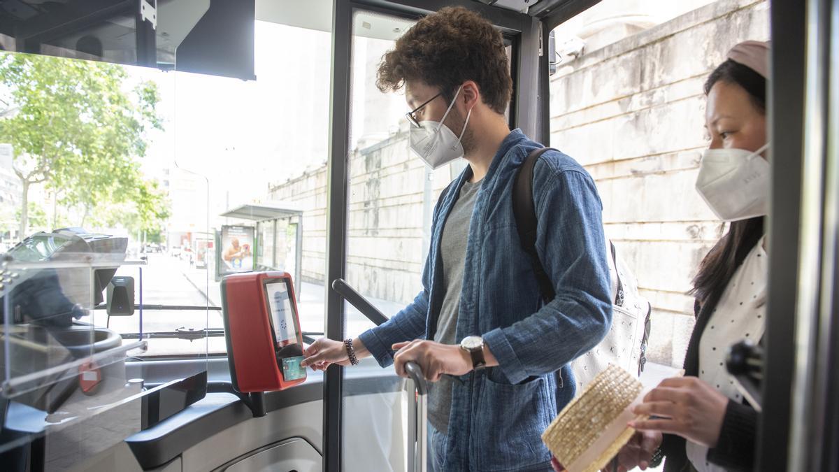 Una pareja de turistas asiáticos paga con tarjeta de créditoel billete de 2,40 euros de la línea 46 de bus al aeropuerto