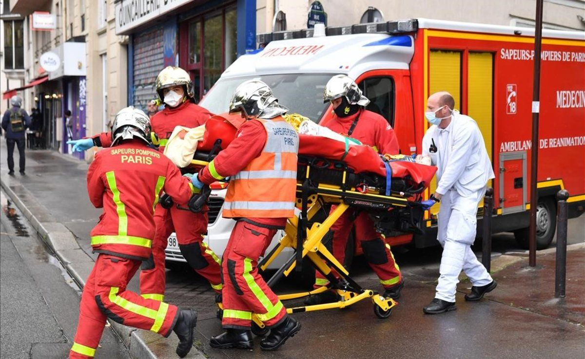 Los bomberos evacúan a un herido en el ataque cerca del semanario Charlie Hebdo.