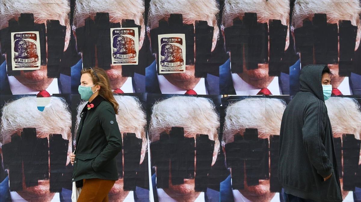 Dos personas caminan ante carteles de Donald Trump tachados, este viernes en Washington.