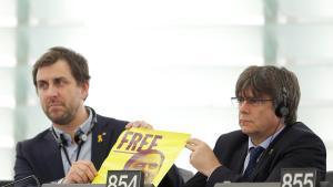Toni Comín y Carles Puigdemont muestran un cartel de Junqueras en sus escaños del Parlamento Europeo, este lunes.
