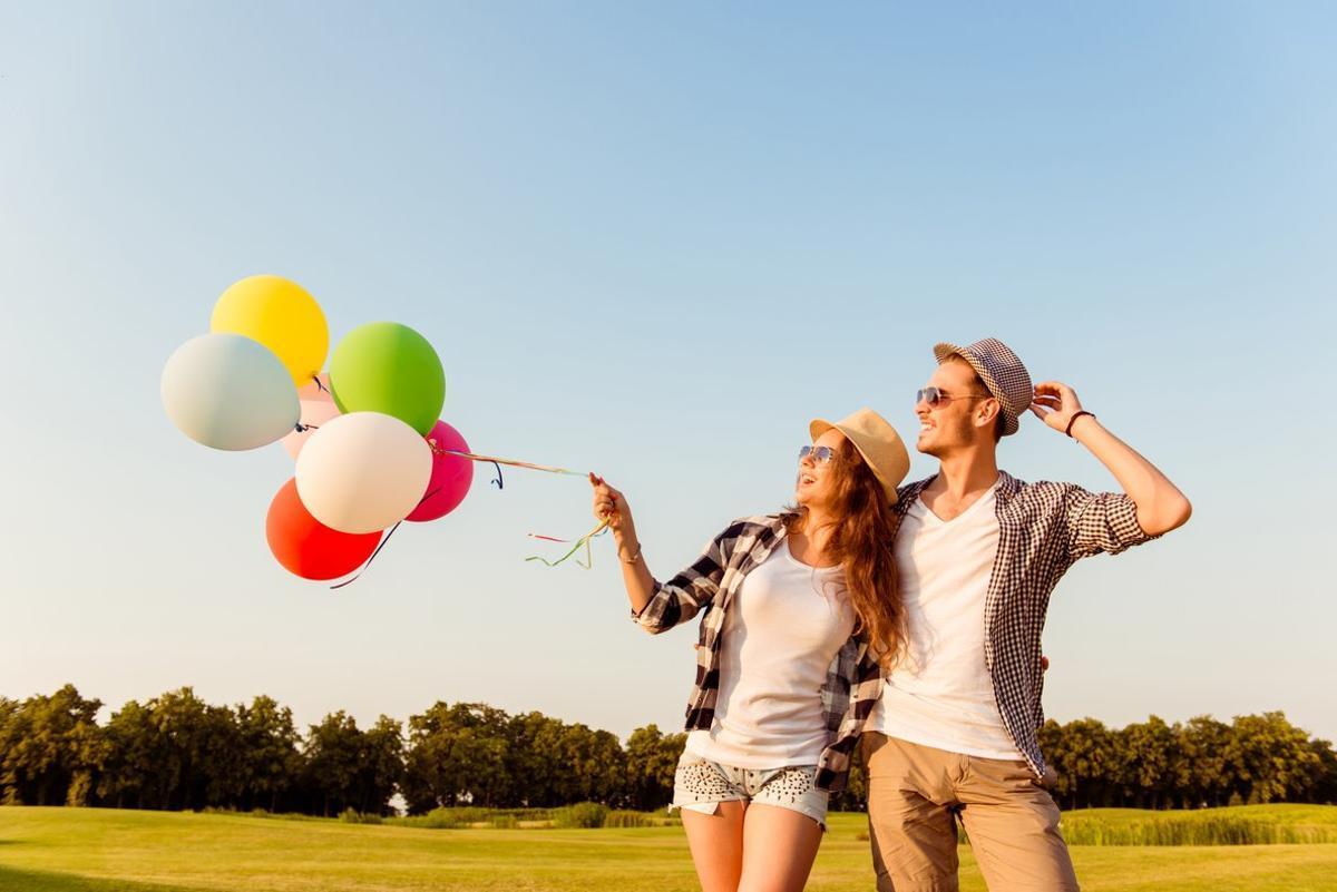 Una pareja riendo con globos.