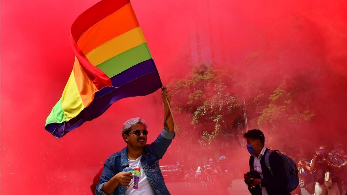 Decenas de personas de la comunidad LGBTmarchan, elsábado, en Ciudad de México.