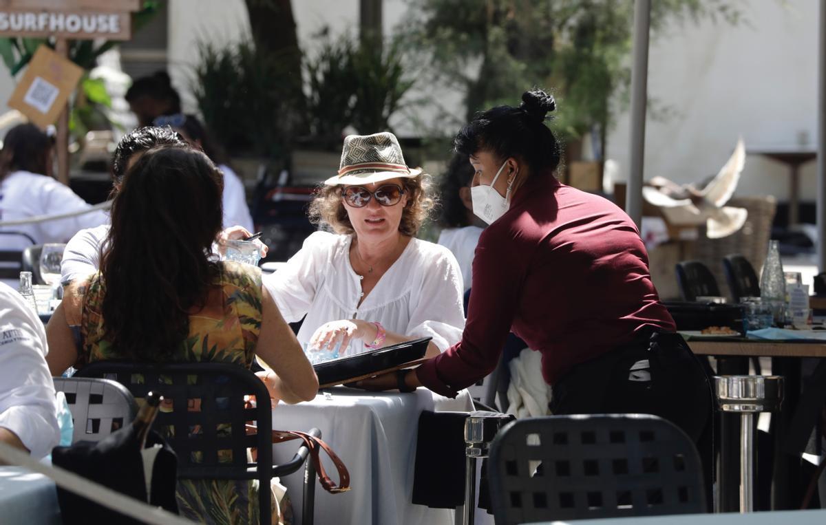 Una camarera atiende a unos clientes en un restaurante de Barcelona.
