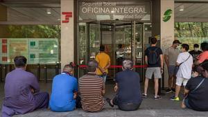 Una decena de personas haciendo cola este verano en una oficina de la Seguridad Social de Barcelona.