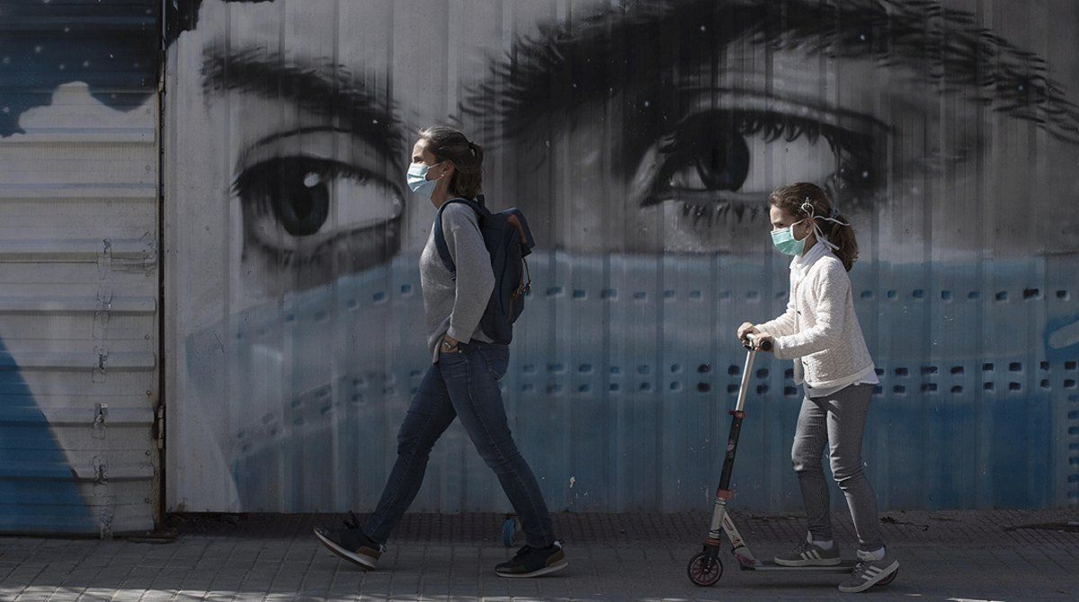 Una mujer y su hija pasean junto al grafiti deuna joven con mascarilla, en Barcelona.