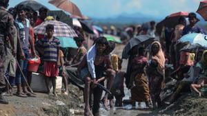 Un refugiado rohinyá lleva a cuestas a un anciano en Bangladés, cerca de la frontera con Birmania.