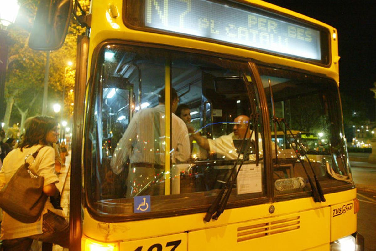 Usuarios del Nitbus suben a un vehículo en plaza de Catalunya.