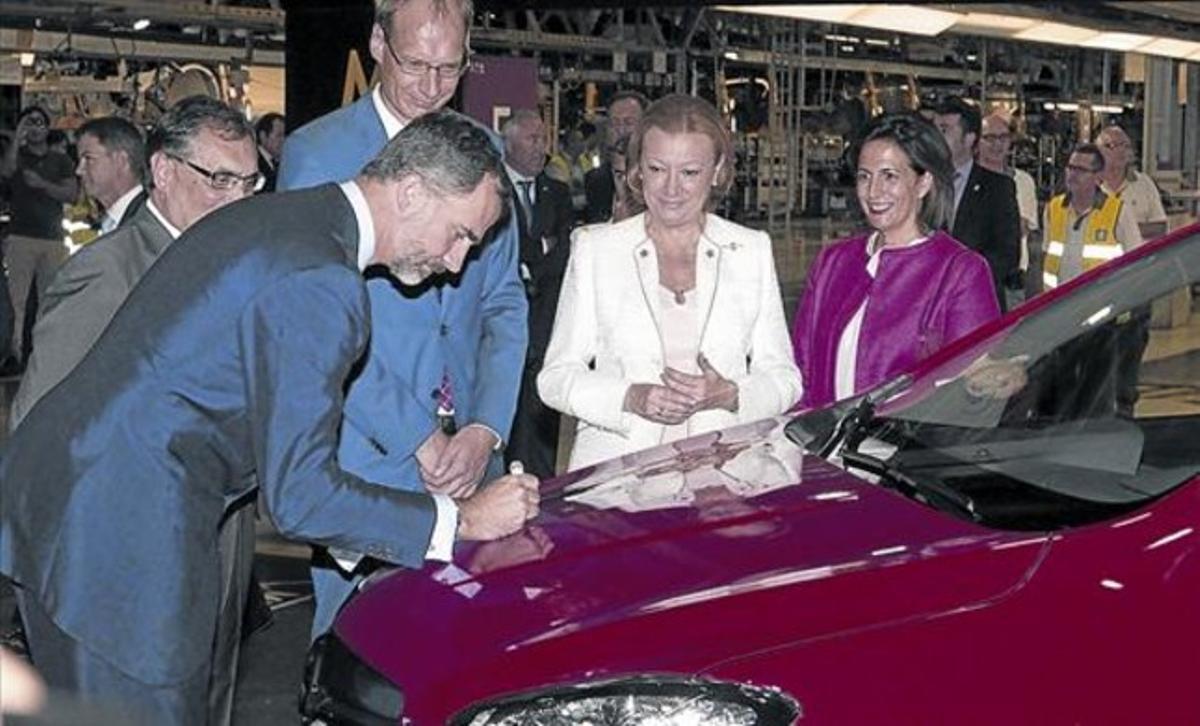 Felipe VI firma en el capó del primer Opel Mokka producido en serie en la fábrica de General Motors en Figueruelas.