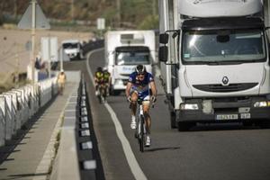 Dos camiones adelantan a unos ciclistas.