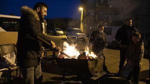 Un grupo de vecinos se calientan en un fuego en la calle porque en sus casas no hay electricidad para encender la calefacción.