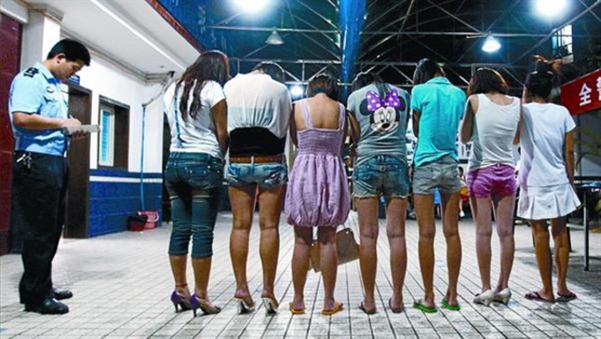 Alineadas. Dos policías custodian a un grupo de prostitutas en Chongging, el pasado día 22 de julio.