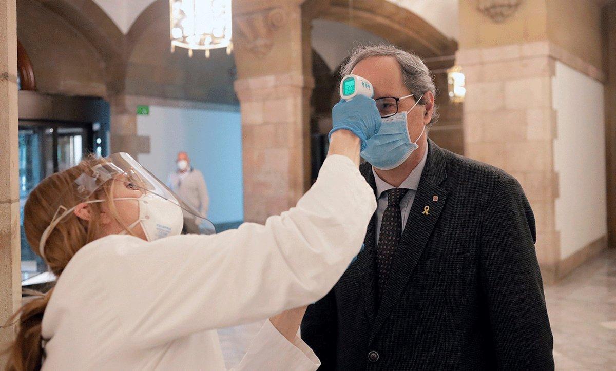 Un miembro de los servicios médicos del Parlament toma la temperatura al presidente de la Generalitat, Quim Torra, a su llegada, el 24 de abril.