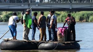 Un grupo de inmigrantes cruza el río Suchiate en unos neumáticos.