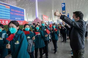 Voluntarios de Wuhan despiden a médicos de Pekín, este miércoles en el aeropuerto de la ciudad china.