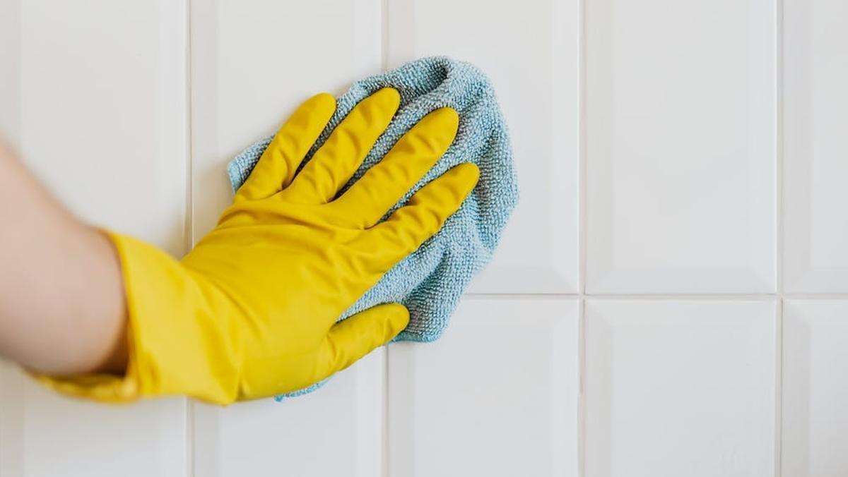 Una persona limpia con una bayeta una pared blanca.