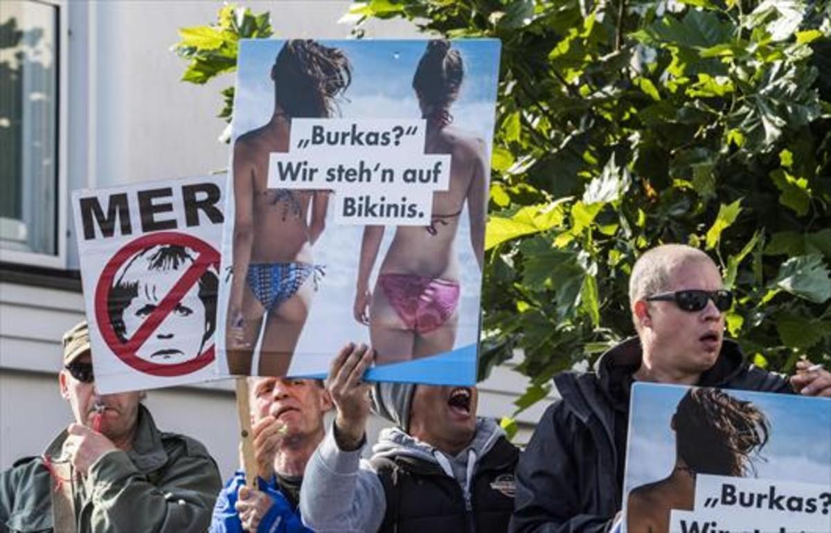 Radicales de la ultraderechista AfD exhiben pancartas contra Angela Merkel y el islam en Ostseebad Bliz, al norte de Alemania.